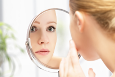 a lady looking in the mirror at her acne scarring